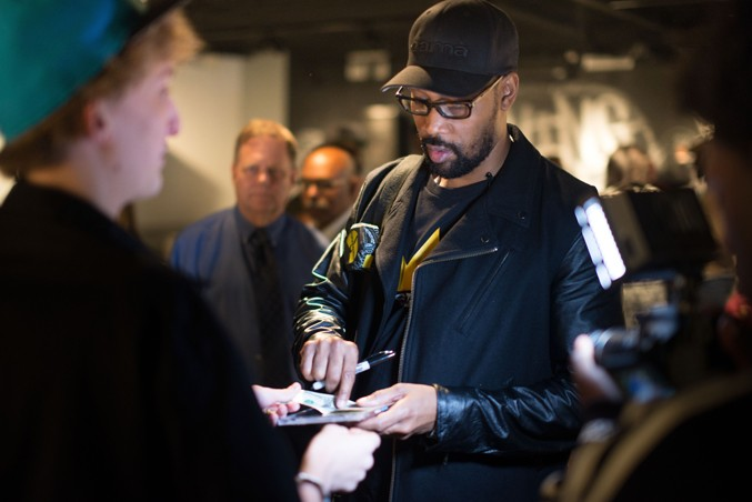 RZA from the Wu-Tang Clan signing autographs during the Living Like Kings opening reception.